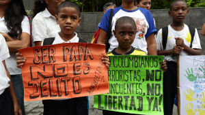 Två barn deltar i en demonstration för mänskliga rättigheter utanför ett FN-kontor i Caracas