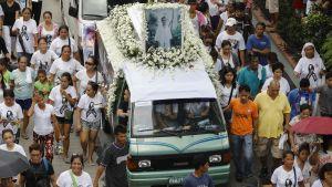 En stor folkmassa ses tåga efter en paketbil med den mördade Kian delos Santos bild på taket.