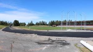 En idrottsplan som renoveras. Ny asfalt har lagts runt gräsplanen i väntan på nya löparbanor.