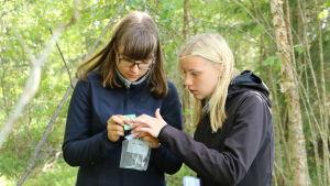 Två tjejer håller i en mottagare i en skog.