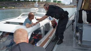 Jari Karlsson, en man i ljusblå t-skjorta, blåser i en alkometer under Sjöbevakningens övervakning till sjöss.