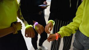 Ungdomar på skoldisko visar fram neonlysande armband