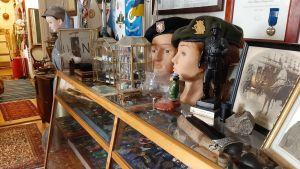 dockor iklädda militära kläder och hyllor fulla av medaljer bakom glas