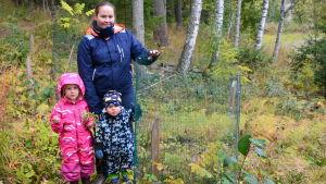 Mamma med två barn vid ett ungträd.
