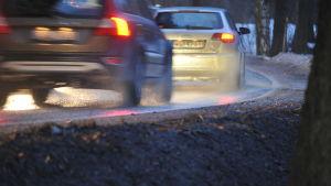 Bilar kör på en våt och glansig landsväg.