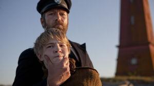 Majakanvartija pitää poikaa väkisin otteessaan, vahva ote pojan leuasta.