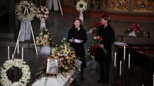 Två kvinnor står vid vit kista som omges av flera blomkransar.