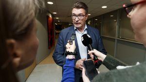 Pros ordförande Jarmo Malinen svarar på journalisternas frågor. Många mikrofoner är ställda mot honom.