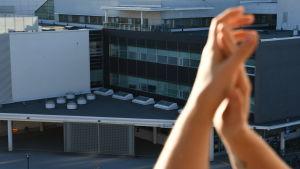 Händer applåderar framför sjukhusbyggnad.