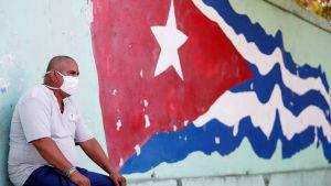 Man med munskydd invid den kubanska flaggan. Havanna, Kuba 21.4.2020