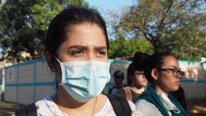 Kvinna ser förbi kameran. Hon bär munskydd.