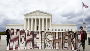 Man och kvinna håller upp skylt där det står ''det här är hemma'' framför USA:s högsta domstol.