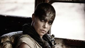 Närbild på Furiosa (Charlize Theron) då hon vänder på huvudet och med allvarligt ansikte ser in i kameran.