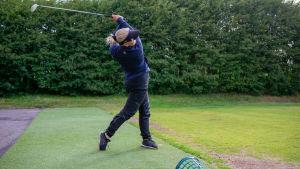 En golfspelare har just slagit iväg bollen.