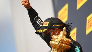 Lewis Hamilton håller upp en knytnäve och har pokalen i andra handen.