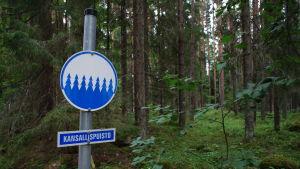 """En skylt med texten """"kansallispuisto"""" i en skog."""