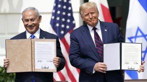 Benjamin Netanyahu och Donald Trump ler framför kamerorna med undertecknade avtal i händerna.