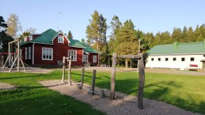 En röd träbyggnad och en ljust stenhus som är Västankvarns skola i Ingå.