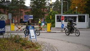Två mopedister i militäruniform åker ut förbi en öppen bom där en person i uniform står och bevakar vid ett vaktbås.
