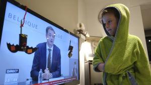 Den femåriga pojken Hugo tittar på regeringens presskonferens med sina föräldrar.