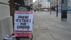 Bild på skylt med text på engelska och tidningar på hög på trattoaren.