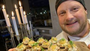 Kocken Micke Björklund visar upp årets självständighetssnacks 2020, forelltartar på rågknappar.