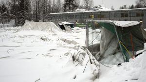 Taket på en uppblåsbar idrottshall ligger på marken , täckt av snö. Till höger syns ett mål.