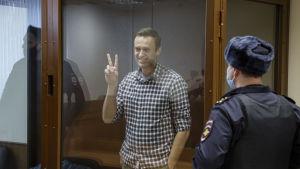 Aleksei Navalnyi näyttää voitonmerkkiä lasiseinän takana