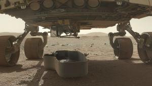 Skyddsskalet för minihelikoptern Ingenuity har lossats från rovern Perseverance på planeten Mars den 21 mars 2021. Skalet är på marken, helikoptern är fortfarande kvar i rovern.