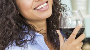 leende kvinna med rödvinsglas