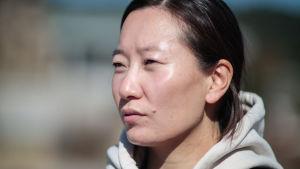Närbild på kvinna med munktröja och svart hår.