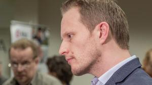 Expert Jussi Sane intervjuas. I bakgrunden syns också en annan man.