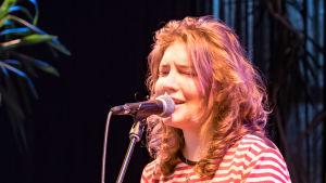 En ung kvinna sjunger in i en mikrofon.