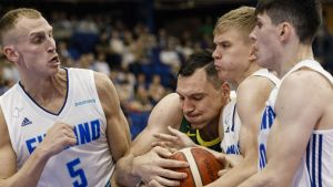 Tre finländska basketlandslagsspelare kämpar om bollen med en litauer.