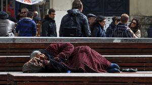 Hemlös kvinna sover på en bänk i Aten, Grekland 6.3.2015.