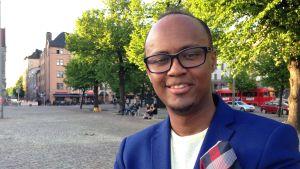 Abdirahim Hussein ler mot kameran på Järnvägstorget i Helsingfors.