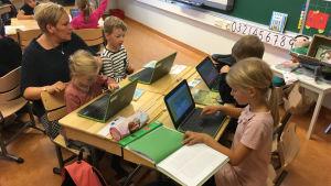 En lärare i ett klassrum med elever som sitter vid sina datorer