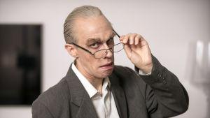 Christoffer Strandberg utklädd till Jörn Donner. Han är sminkad för att se gammal ut samt har stora ögonbryn. Han har också på sig en säckig kavaj och glasögon.