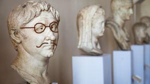 Grekisk staty med efteråt ritade glasögon och mustasch