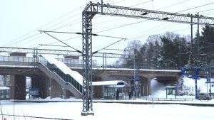 En vintrig dag på järnvägsstation i Karis där man ser järnvägsbron.
