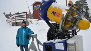 Niklas Westerlund bredvid en av snökanonerna vid Finby skidstadion