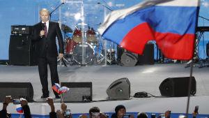 Vladimir Putin står på en scen intill en rysk flagga.