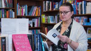 Anna-Lena Palomäki omgiven av bokhyllor.
