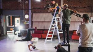 Ett kamerateam filmar en ung man som dansar breakdance.