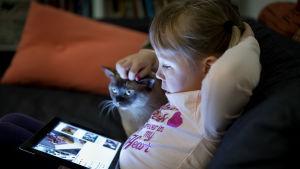 Kaisla 5 år tittar på Ipad. På bilden även familjens katt.