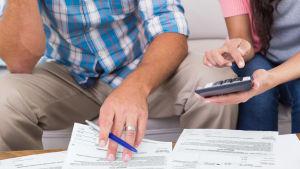 Vi ser händerna av en man och en kvinna. På ett bord ligger en massa räkningar. Mannen håller i en penna och kvinnan en miniräknare.