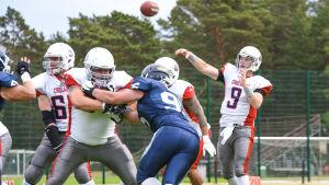 En quarterback kastar bollen i en tajt situation.
