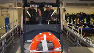 Fören på en räddningsbåt. Man ser den lilla täckta förarhytten. Det står Babben och Hanko på hyttfönstret. man ser också några orangefärgade livbojar.
