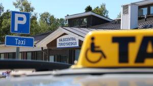 Ingången till HVC i Närpes. I förgrunden skymtar en gul taxiskylt.