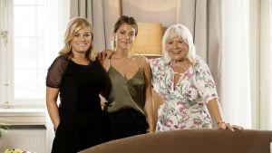 Tre kvinnor i olika åldrar poserar bakom soffa